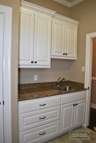 White laundry room with drawers