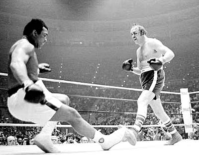 Defending heavyweight champion Muhammad Ali goes down in the ninth round of the title bout against challenger Chuck Wepner, from Bayonne, N.J., at the Richfield Coliseum, in Cleveland, Ohio, on March 24, 1975. Ali tripped over Wepner's foot, but the referee ruled it as a knockdown. Ali later knocked out Wepner in the 15th round to retain his title. (AP Photo)