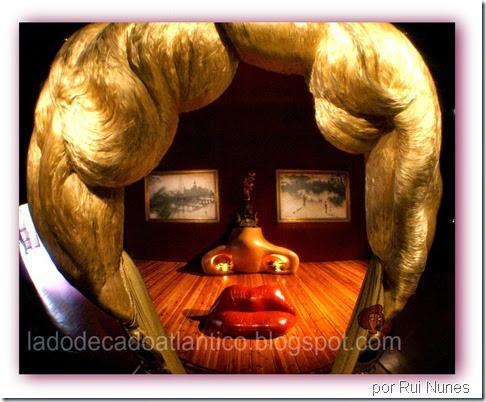 Foto a partir de lente focando o sofá-lábios, lareira, candelabro e quadros da sala Mae West,  na Casa Teatro-Museu Dalí em Figueres, Espanha