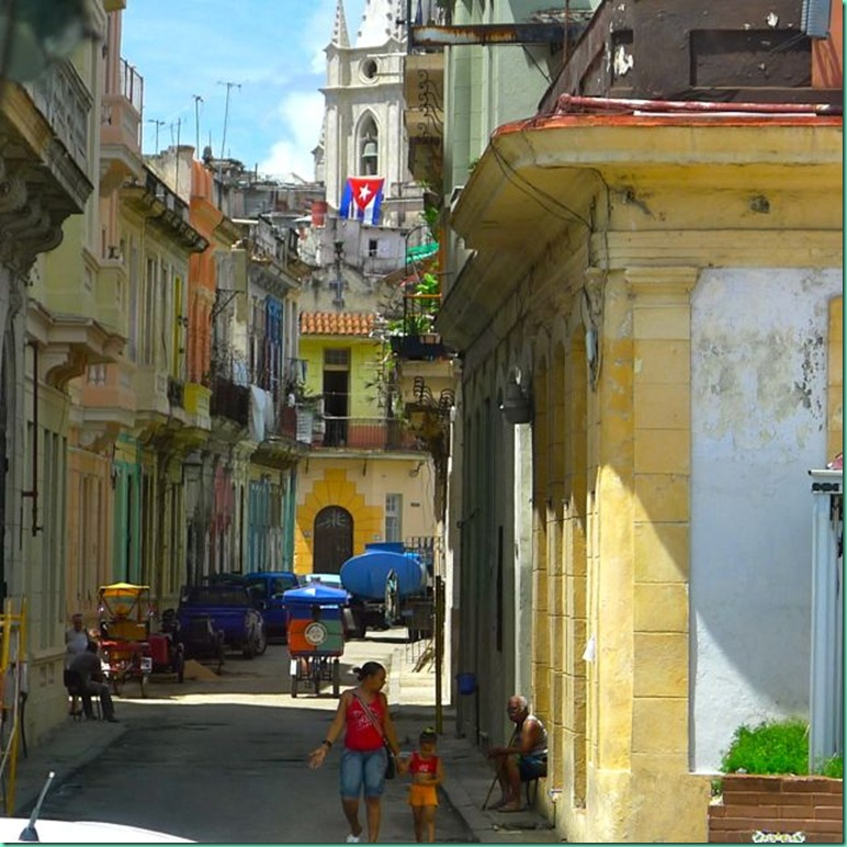 street scene, tropical colored buildings, cathedral, Cuba flag, Havana, Habana Vieja