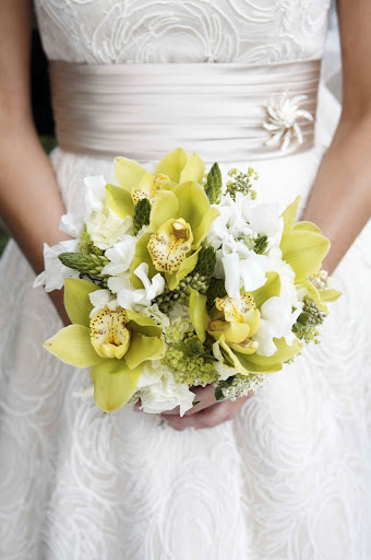Cymbidium orchids, star of Bethlehem, lady's mantle, and  seeded eucalyptus create a soft yet textural bouquet.  Photo by Milton Morris.