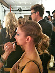 The curls of the ponytail are pinned in place (so they don't loosen up before the show), but, here, you can see the silhouette Tommy was going for: A twirled lock in front, volume at the crown, and a bouncy, pony finish.