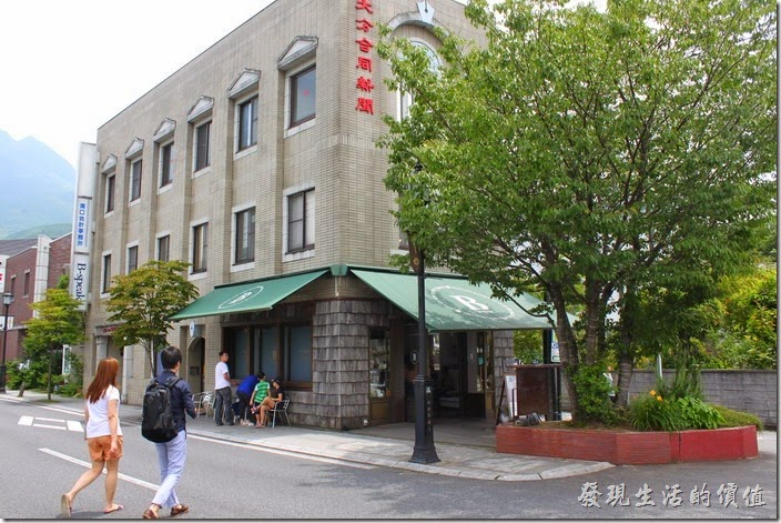 日本-由布院B-SPEAK瑞士捲。【B-SPEAK】就在這棟有著【大分合同新聞】的幾個紅色大字建築的一樓。因為門前有顆還蠻高的樹木,稍微擋住了它的視線。