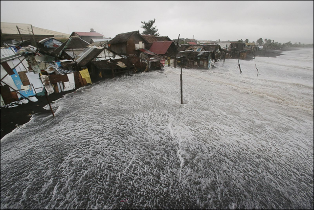 Strong waves crash into coastal houses as Typhoon Hagupit pounds Legazpi, Albay province, eastern Philippines, 7 December 2014. Photo: Aaron Favila / AP Photo