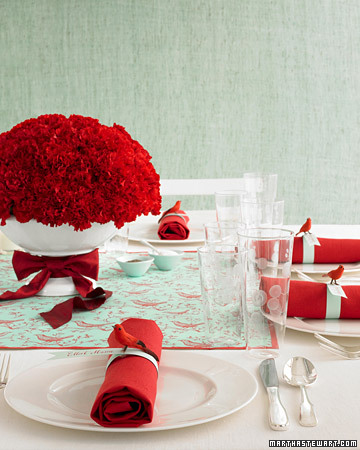 Bold accents such as a carnation centerpiece or red napkins pop against white table linens and plates.