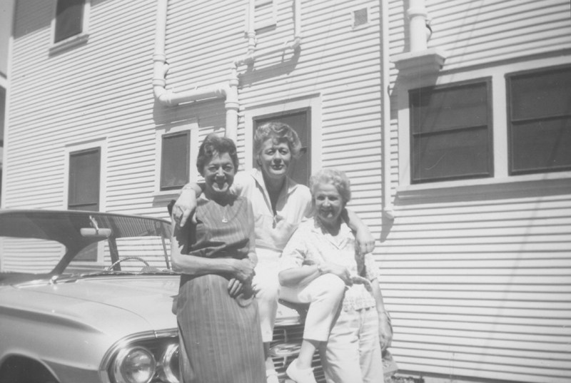 Kay, Geri, and Lois Mercer sitting on a car. Undated.