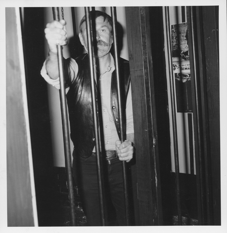 "Mark Annav, owner of the MARK IV Health Club, poses behind bars at a Silver Lake leather bar, symbolizing his and 39 others' arrest when  Los Angeles Police raided his club for holding a ""slave auction"" fundraiser. April 1976."