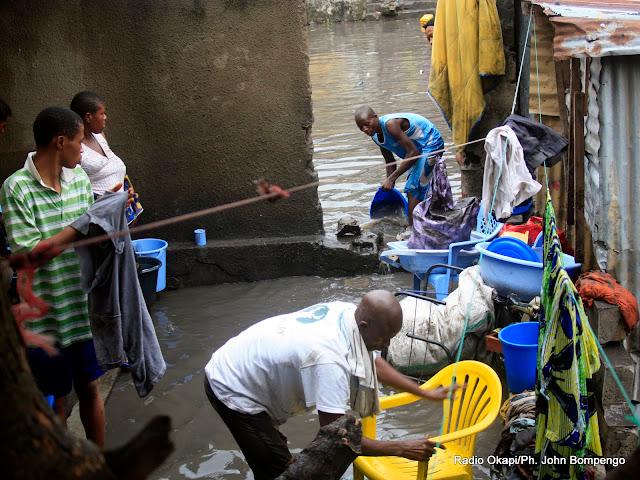 Une famille inondée par les eaux de pluie, tente de récupérer  leurs biens en évacuant les eaux stagnantes dans la parcelle. Radio Okapi/Ph. John Bompengo