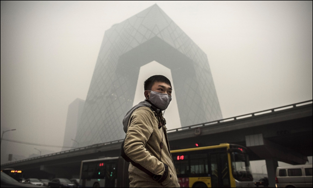 A man stands in front of the CCTV building in Beijing, wearing a filter against the dense smog. Beijing's air quality has long been a cause of concern, but the effects of its extreme levels of pollution can now been seen in physical changes to the architecture of the city. Photo: Kevin Frayer / Getty Images