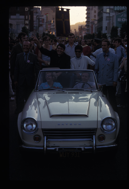Reverend Troy Perry  (in black) with his partner, Steve Jordan, and Perry's mother, Edith Allen Perry (front seat) feted in a car at Los Angeles' first Christopher Street West pride parade. 1970.