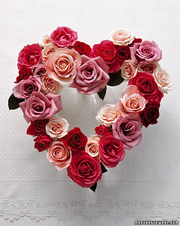 Arrange roses in the shape of a heart for a romantic centerpiece by cutting their stems short.