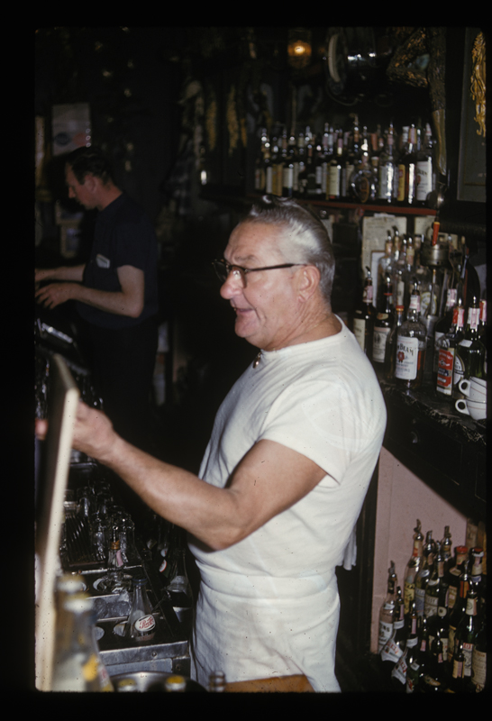 Bartender serves drinks during Jose Sarria's drag show at the Black Cat Bar. Circa early 1960s.