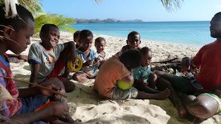 John (rechts) öffnet grüne Kokosnüsse für die Kinder zum Trinken.