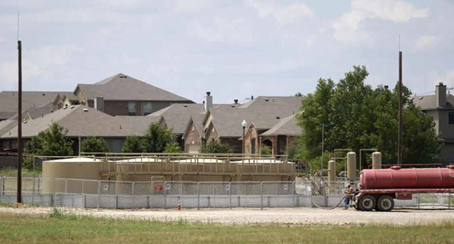 Natural gas well holding tanks sit next to a subdivision of homes in Denton, Texas, Thursday, 29 May 2014. This North Texas city wants less gas and more hot sauce. Unlike most Texas communities that have embraced the lucrative oil and natural gas booms, Denton leaders are considering a petition to ban hydraulic fracturing and are trying to persuade Sriracha to move its massive pepper-grinding operations from California. Although sitting on top of the Barnett Shale, believed to hold one of the largest natural gas reserves in the U.S., Denton would rather be known for having the largest community garden in the U.S. Photo: LM Otero / AP