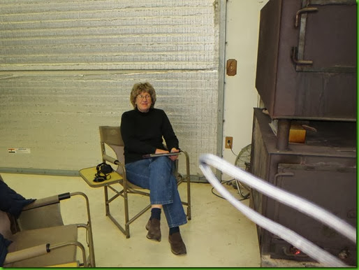 Lynne enjoying the wood stove at Little House Customs