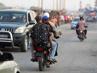 Les routes de Kinshasa n&#039;ont pas des voies spcifiques pour les motos. Motards et conducteurs des autres vhicules roulent sur les mmes voies. Les passagers des motos nhsitent pas  dcrocher leurs tlphones pendant quils roulent.