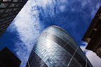 "30 St Mary Axe, also known as ""the Gherkin"" is a skyscraper  in London's financial district completed in December 2003, with height of 180 meters and 41 floors."