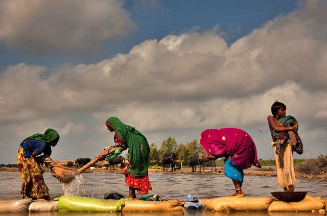 A flood-affected family in Pakistan washing clothes in rising floodwaters next to their temporary camp in Digri, Sindh province. UN