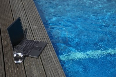 6275266-notebook-computer-lying-next-to-a-swimming-pool