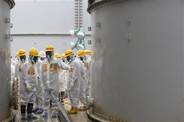 In this photo provided by Nuclear Regulation Authority (NRA), NRA commissioners inspect storage tanks used to contain radioactive water at the Fukushima Dai-ichi nuclear power plant, operated by Tokyo Electric Power Co. (TEPCO), in Okuma in Fukushima prefecture, northern Japan, 23 August 2013. Deep beneath Fukushima's crippled nuclear power station a massive underground reservoir of contaminated water that began spilling from the plant's reactors after the 2011 earthquake and tsunami has been creeping slowly toward the sea. Now, 2 1/2 years later, experts fear it is about to reach the Pacific and greatly worsen what is fast becoming a new crisis at Fukushima: the inability to contain vast quantities of radioactive water. Photo: Nuclear Regulation Authority / AP