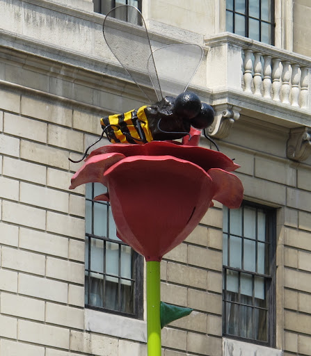 A fiberglass and resin bee perches atop a beautiful bloom.