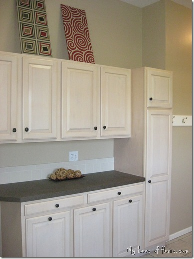 Maple cabinets, brown counter tops, red fabric wall art, beige walls, white woodwork