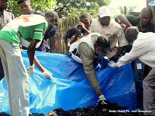 Des volontaires, des policiers et les membres de la Croix Rouge National, tentent de dégager les corps calcinés ce 20/05/2011 à Kinshasa, lors d'un incendie qui avait tué six membres d'une même famille. Radio Okapi/ Ph. John Bompengo