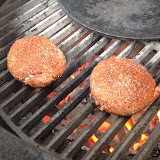 Old-school burger cooking over an open flame.