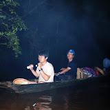 ロングハウスへ向かう道中、暗闇の中増水した川をボートで進む / Passing through a swollen stream on a boat to visit a longhouse