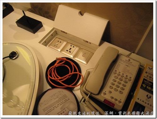 深圳寶利來國際大酒店,書桌旁還貼心的準備了萬用插座,其電壓當然都是220V,但現在的變壓器幾乎都是100~240V通吃,所以應該無所謂。網路接口當然也準備好囉!