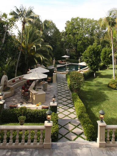 Wide view of outdoor patio with view of outdoor kitchen, manicured lawn, walkway, umbrellas over bar area, pool, tropical scenery, and various hedges.