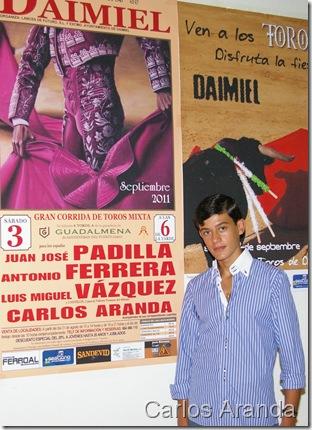 Carlos Aranda junto al carte que anuncia su presentacion en su pueblo