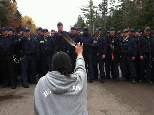A woman holds up a feather in front of policemen at the New Brunswick fracking blockade, 18 October 2013. Photo: Ossie Michelin / APTN
