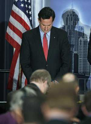 Rick Santorum bows his head during a prayer before addressing the Detroit Economic Club, 16 February 2012. Bill Pugliano / Getty Images