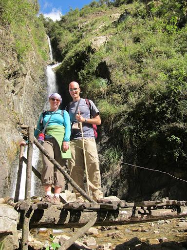 Crossing a rickety bridge near a waterfall.