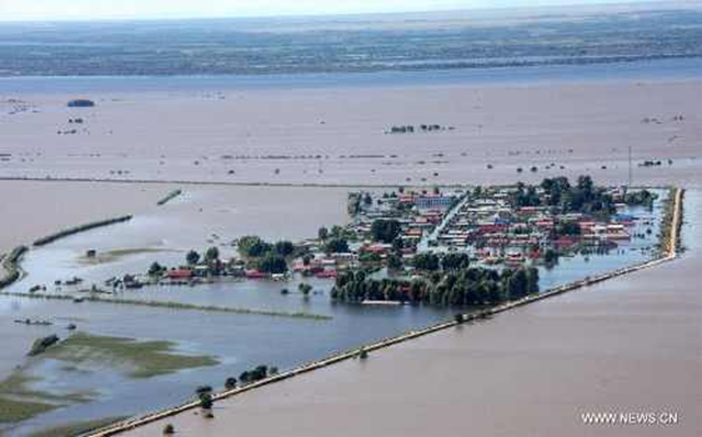 The aerial photo taken on 26 August 2013 shows houses inundated by floods along the Tongjiang-Fuyuan river section of the Heilong River in northeast China's Heilongjiang Province. The Heilong River has swelled since mid-August, with some sections of its middle and lower reaches seeing their worst floods in history. Photo: Ma Ling / Xinhua