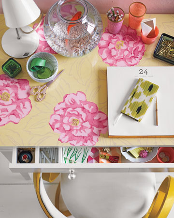 Her work will always be more pleasant with flowers on the desk. Place a swath of bloom-themed wallpaper (use double-sided tape if the edges curl) on a desk, and then top it with a piece of custom-cut glass. (marthastewart.com)