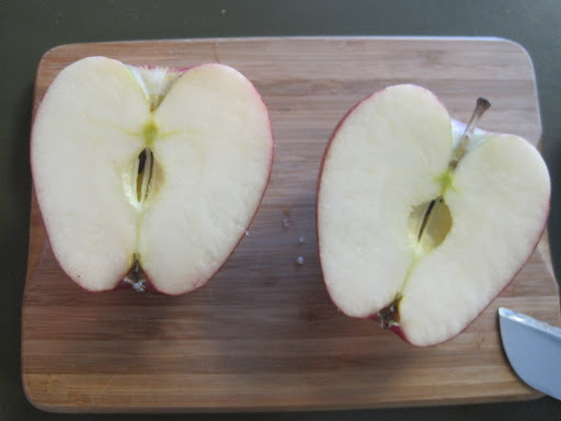Step one: Slice the apples in half.  Use paper towels to dab away excess moisture on the cut surface before you dip into paint.