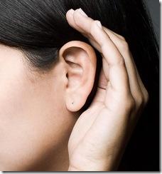 Pessoa vista de perfil, com a mão em concha na orelha