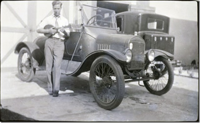 Arthur Iverson holding a mandolin standing in front of an automobile