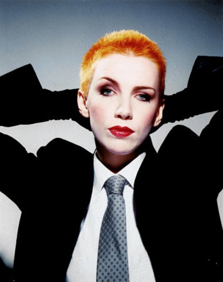 Annie Lennox wearing her classic suit and short orange hair