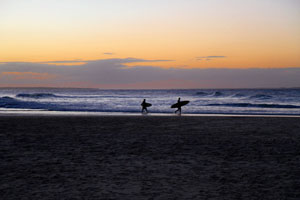 Two lone surfers at sunset