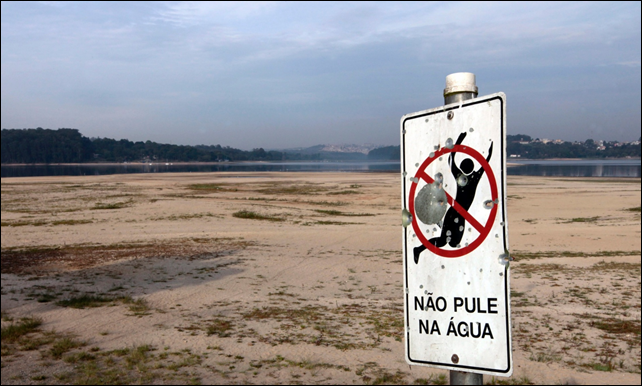 A sign reading 'Don't jump in the water' at the dried up part of the Guarapiranga reservoir in November 2014. Photo: Paulo Whitaker / Reuters