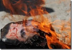 Syria protest Assad face burnt