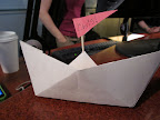 Once the boats are folded, attaching a tootpick mast and paper flag transforms them into placecards.  You could step this step - and the sharp objects - and just write on the boats.