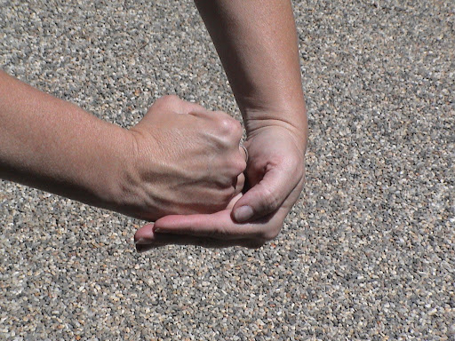 Close your hand to make a fist, similar to the Heimlich technique commonly performed on humans.