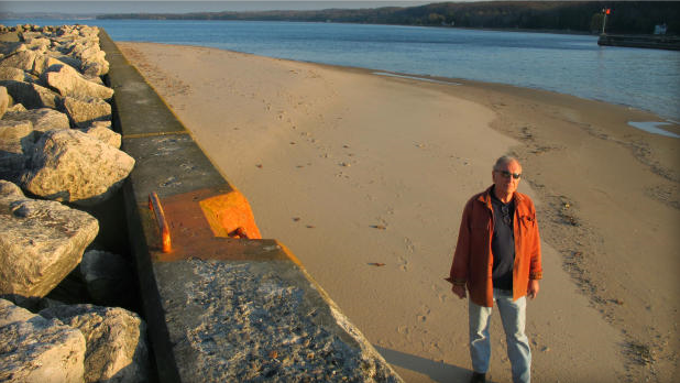 In this 16 November 2012 photo, Jim Simons, who runs a rod and reel repair business in Onekama, Michigan, strolls on a sand bar alongside the Portage Lake channel that leads to Lake Michigan at Onekama. The sand bar normally would be submerged in water, but low Great Lakes levels have exposed the shoreline in many areas, causing problems for boaters and tourist businesses in small harbor towns. The Great Lakes, the world's biggest freshwater system, are dropping because of drought and climbing temperatures, a trend that accelerated with this year's almost snowless winter and scorching summer. John Flesher / AP Photo