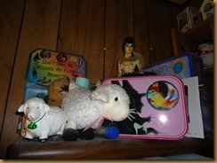 This is the top shelf of the bookcase that is next to the computer.  The bookcase is filled with teacher resources and one shelf of crochet books/patterns.  The doll was brought back from Vietnam by my father in 1971.  I just started collecting sheep.  Behind the sheep are more Wiz of Oz figurines.  The other lunch box, which I have used.  The wiz of Oz board game, and tucked in front is a piece of art I won from a blog.  I don;t have a spot for it yet.