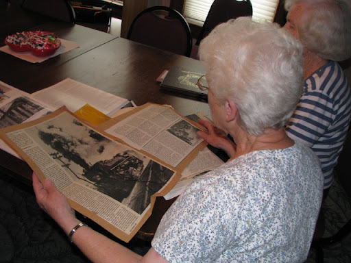 Betty Perry, president of the Cabool History Society, looks over old documents and articles with a fellow member of the Cabool History Society.