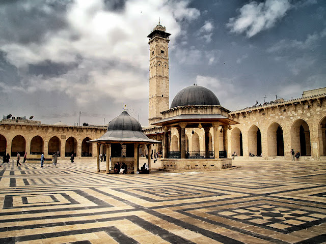 "Great Mosque of Aleppo, early 8th century, view of the courtyard and minaret The Great Mosque is still the most important religious site in the city. It was founded in the early 8th century, probably by Sulaiman ibn Abd al-Malik shortly after the Muslim conquest of Aleppo. Its slim, square minaret, which was built in 1094 during the reign of the Seljuk prince,Tutush, on the orders of the judge Abu l-Hasan Ibn al-Khashshab, is one of the architectural gems of northern Syria. This six-story structure is divided by Kufic and naskhi inscriptions, and ""classicizing'architectural details, such as continuous moldings, pilasters, and elaborate trefoil and polyfoil arches. The architect of this minaret was Hasan ibn Mufarraj al-Sarmini, who was also responsible for the minaret at Maarrat al-Numan."